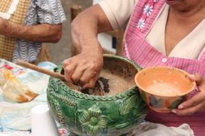 A woman prepares champurrado.
