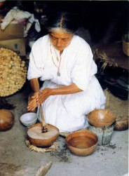 Woman using molinillo to froth chocolate beverage.
