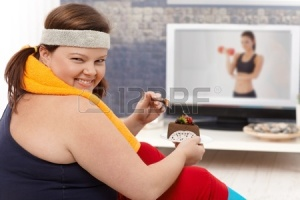 "A stock image that embodies negative connotations about chocolate (such as laziness and obesity). The concerning caption of this image is ""Fat woman choosing chocolate cake instead of doing gymnastics, smiling happily."""